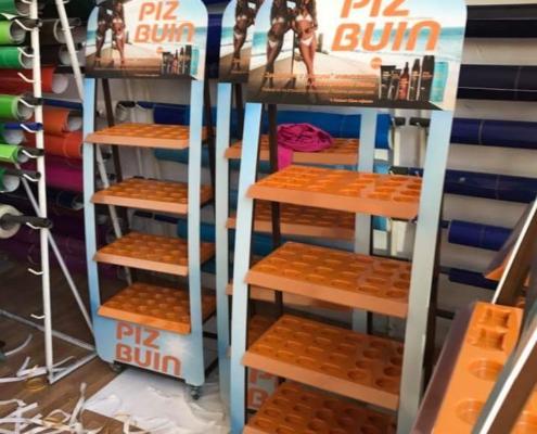 Метални стелажи за Piz Buin с вакуум формовани поставки за различните козметични продукти на марката.